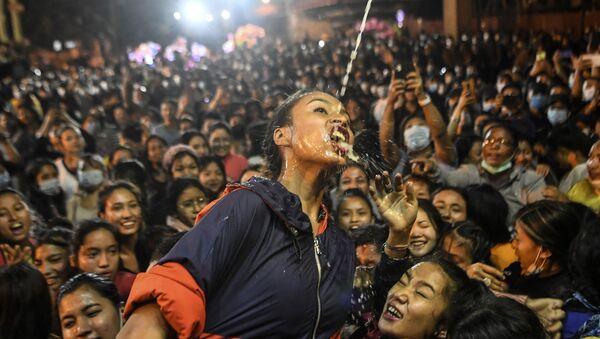 Девушка пьёт вино из статуи Швет Бхайрава во время фестиваля Индра Джатра в Катманду - Sputnik Azərbaycan