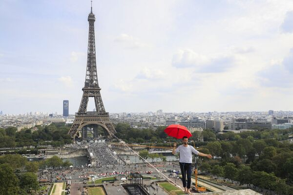 Французский канатоходец Натан Полен идет по канату между Эйфелевой башней и театром Шайо. - Sputnik Азербайджан