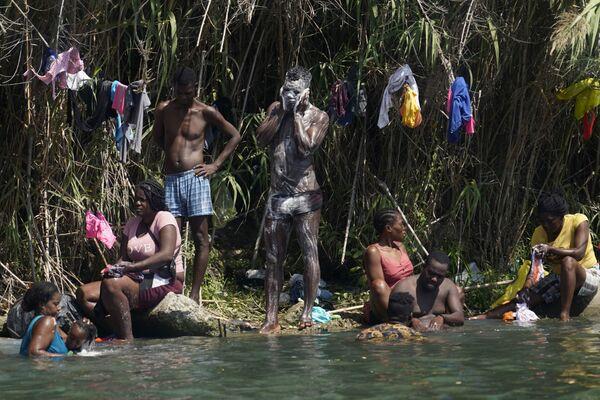 Гаитянские мигранты купаются и стирают на берегу Рио-Гранд, США. - Sputnik Азербайджан