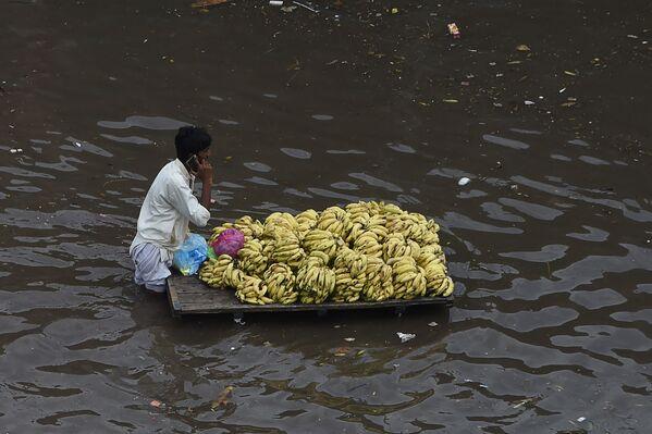 Продавец фруктов c тележкой на затопленной после проливного дождя улице в Лахоре, Пакистан. - Sputnik Азербайджан