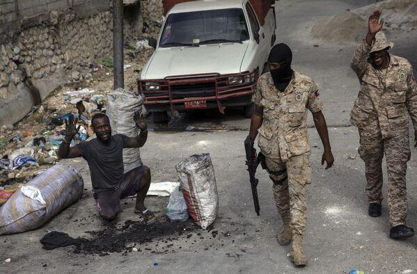 Мужчина поднимает руки, когда полицейские патрулируют улицы в центре города Порт-о-Пренс, Гаити. - Sputnik Азербайджан