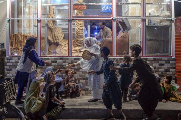 Женщина раздает хлеб нуждающимся детям перед пекарней в Кабуле. - Sputnik Азербайджан