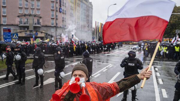 Человек с флагом Польши в Варшаве, фото из архива - Sputnik Азербайджан