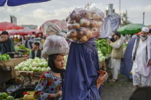 Женщина в парандже несет на голове мешок с луком на рынке в Кабуле. - Sputnik Азербайджан