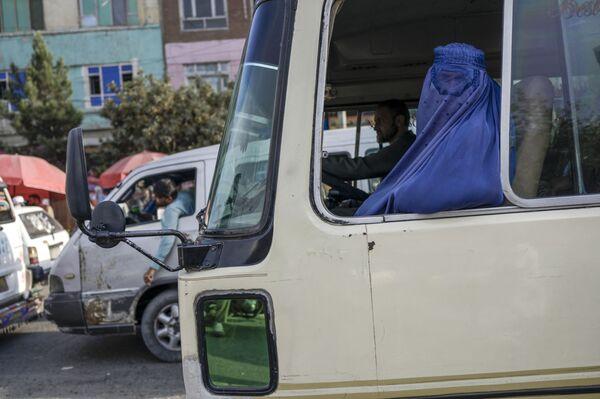 Женщина в парандже едет на  автобусе по Кабулу. - Sputnik Азербайджан