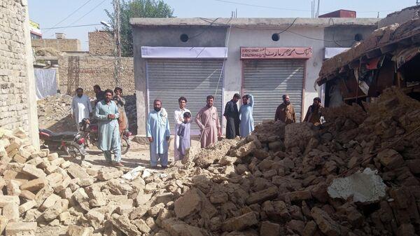 Жители возле разрушенного дома после землетрясения в Харнае, Пакистан - Sputnik Азербайджан