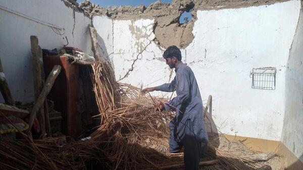 Местный житель возле разрушенного дома после землетрясения в Харнае, Пакистан - Sputnik Азербайджан
