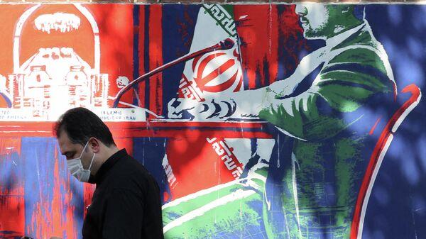 Мужчина проходит мимо фрески с изображением иранского чиновника в гражданской одежде в Тегеране - Sputnik Азербайджан