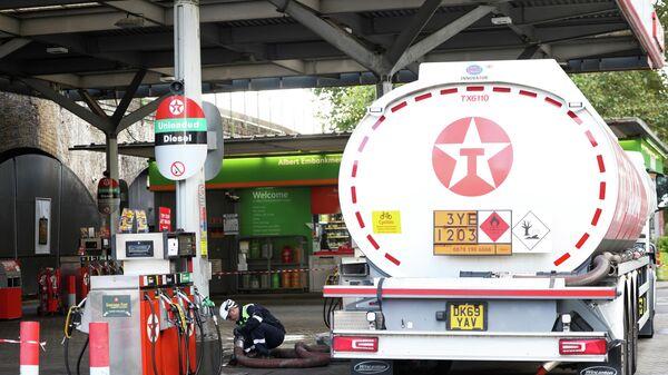 Водитель грузовика доставляет топливо на заправочную станцию в Лондоне - Sputnik Азербайджан