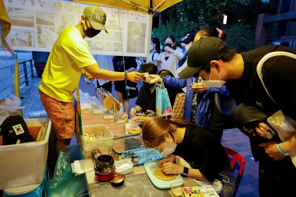 Уличный торговец в Сеуле штампует форму зонтика на далгоны, хрустящей сахарной конфеты, показанной в популярном сериале Netflix Squid Game. - Sputnik Азербайджан