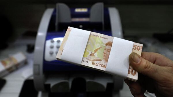 Сотрудник обменного пункта держит в руках банкноты турецких лир, фото из архива - Sputnik Азербайджан