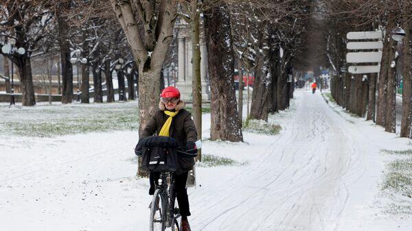 Человек едет на велосипеде по Елисейским полям после небольшого ночного снегопада в Париже - Sputnik Азербайджан