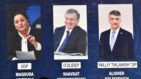 Люди проходят перед рекламным щитом с изображениями кандидатов в президенты Узбекистана - Sputnik Азербайджан