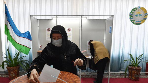 Женщина голосует на избирательном участке во время выборов президента Узбекистана - Sputnik Азербайджан