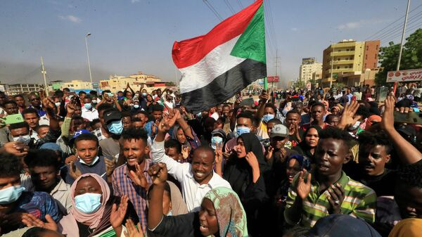 Суданские протестующие поднимают национальные флаги во время митинга в столице Хартуме - Sputnik Азербайджан