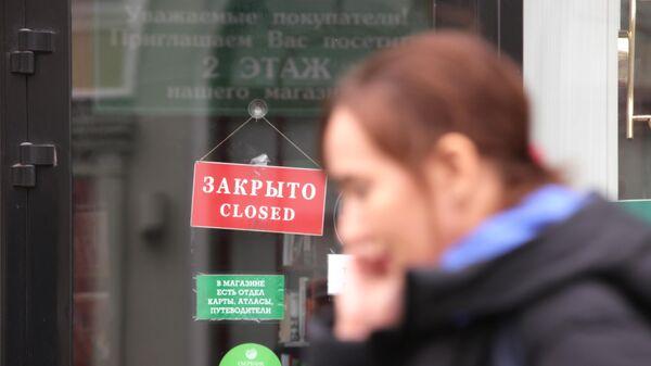 Женщина проходит мимо витрины магазина в Москве - Sputnik Азербайджан