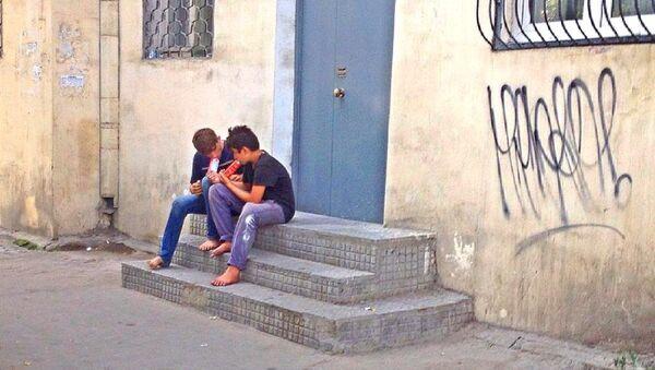 Двое беспризорников на скамейках у жилого дома нюхают клей. - Sputnik Азербайджан