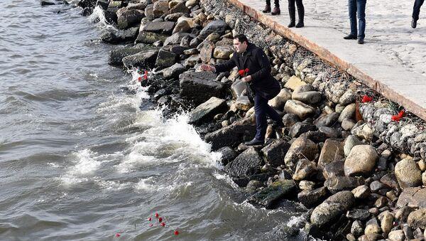 Мужчина бросает гвоздики в море - Sputnik Азербайджан