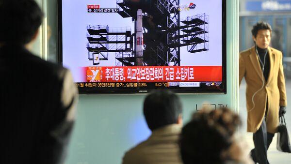 Туристы на железнодорожном вокзале в Сеуле смотрят новость о запуске ракеты - Sputnik Азербайджан