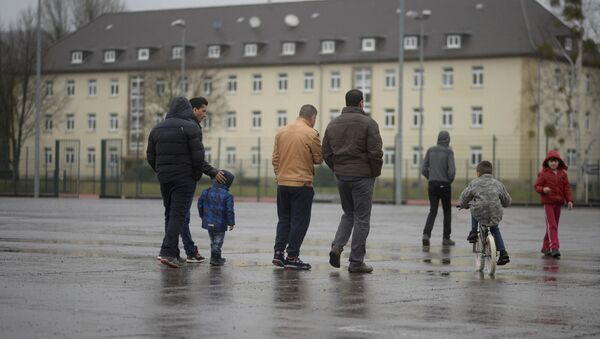 Мигранты и их дети гуляют на территории лагеря для беженцев в Гамельне, Нижняя Саксония - Sputnik Азербайджан