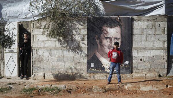 Жители пригорода Дамаска стоят возле плаката президента Башара Асада - Sputnik Азербайджан