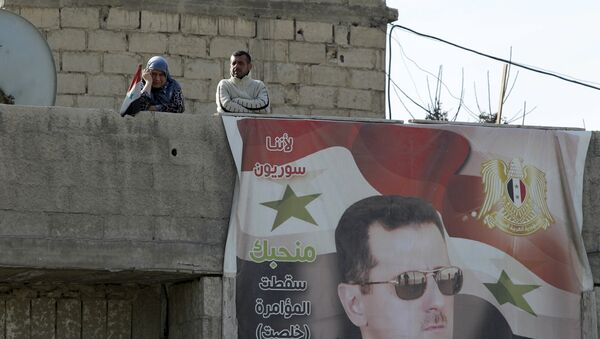 Жители лагеря Вафиден возле картины президента Сирии Башара Асада в пригороде Дамаска - Sputnik Азербайджан