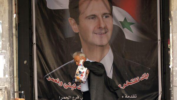 Мужчина проходит рядом с плакатом Башара Асада в столице Сирии Дамаске - Sputnik Азербайджан