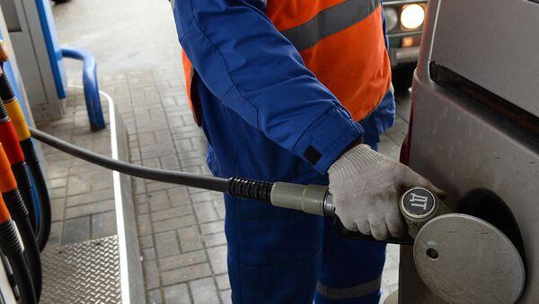 Заправщик заправляет автомобиль на автозаправочной станции - Sputnik Azərbaycan