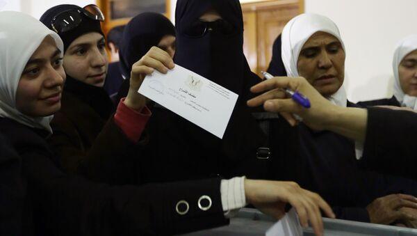 Сирийская женщина голосует на одном из избирательных участков Дамаска - Sputnik Азербайджан
