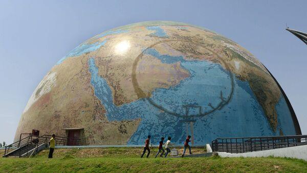 Индийские дети играют вокруг павильонa Планета Земля, расположенного в университетском городке Гуджарат - Sputnik Азербайджан