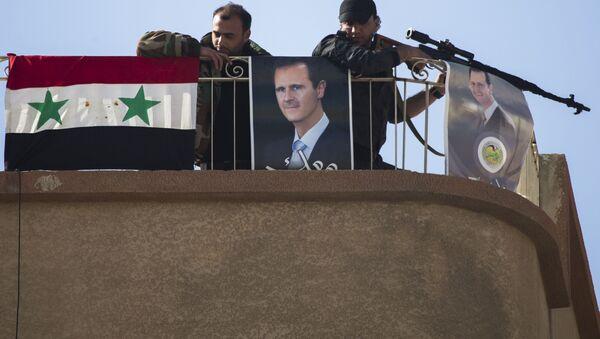 Солдаты сирийской армии рядом с фотографией президента Башара Асада в городе Эт-Талль, Сирия. Архивное фото - Sputnik Азербайджан