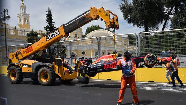 Кран поднимает автомобиль австралийского водителя Red Bull Racing Даниэля Риккардо после аварии на Бакинской городской трассе - Sputnik Азербайджан