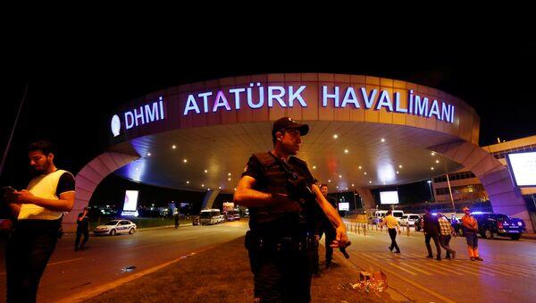 Полицейский стоит на страже у входа в аэропорт имени Ататюрка в Стамбуле, Турция, после теракта - Sputnik Азербайджан
