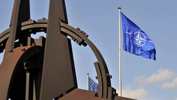 Эмблема и флаг НАТО перед зданием Альянса в Брюсселе - Sputnik Азербайджан