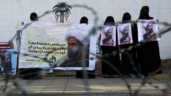 Женщины держат в руках плакаты с изображением шиитского клерка Нимр аль-Нимра, казненного в Саудовской Аравии. Архивное фото - Sputnik Азербайджан