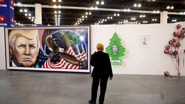 Охранник рассматривает иллюстрации на стене с изображениями кандидатов в президенты США Дональда Трампа и Хиллари Клинтон. Пасадина, Калифорния - Sputnik Азербайджан
