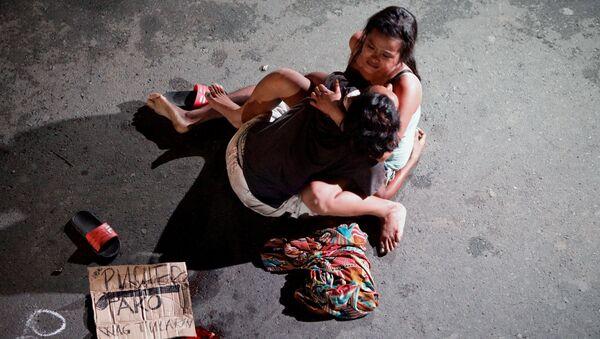 Девушка обнимает тело своего партнера, который был убит на улице бригадой дружинников. Филиппины, Манила. 23 июля 2016 года - Sputnik Азербайджан