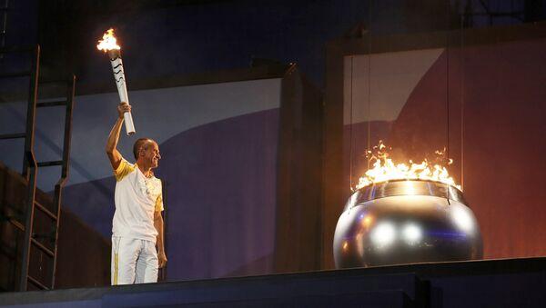 Бразильский бегун-стайер Вандерлей Кордейру зажигает Олимпийский огонь на цереомнии открытия Игр - Sputnik Азербайджан