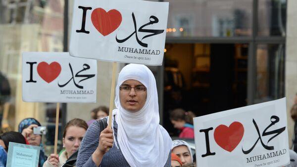Женщина во время акции в поддержку мусульман держит плакат с надписью Я люблю Мухаммеда, Германия, Гамбург, 29 сентября 2012 года - Sputnik Азербайджан