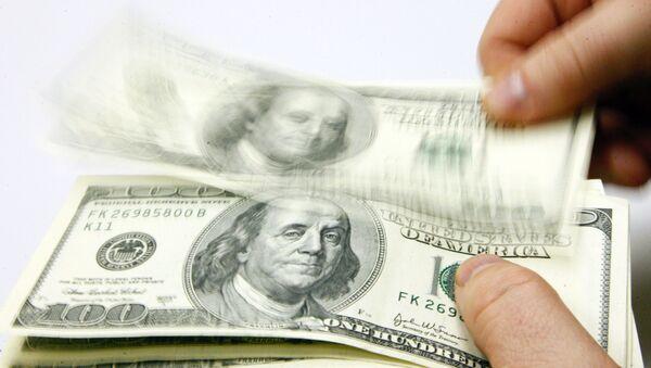 Мужчина пересчитывает доллары США, фото из архива - Sputnik Azərbaycan