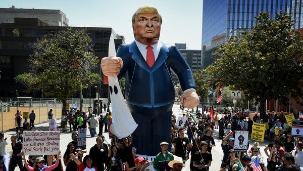Члены Коалиции по защите прав мигрантов выкрикивают лозунги против Трампа в Лос-Анджелесе, штат Калифорния на 1 мая 2016 - Sputnik Азербайджан