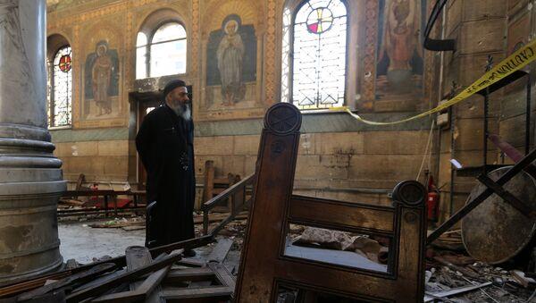 Коптский священник стоит на месте взрыва внутри собора в Каире, 11 декабря 2016 года - Sputnik Азербайджан