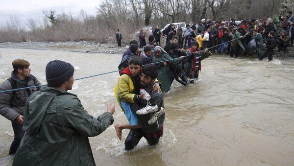 Беженцы переходят через реку вблизи греко-македонской границы, к западу от деревни Идомени, Греция, 14 марта 2016 года - Sputnik Азербайджан