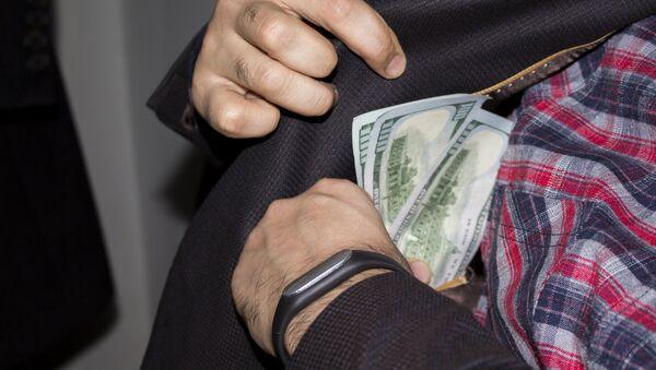 Мужчина прячет деньги во внутренний карман, фото из архива - Sputnik Azərbaycan