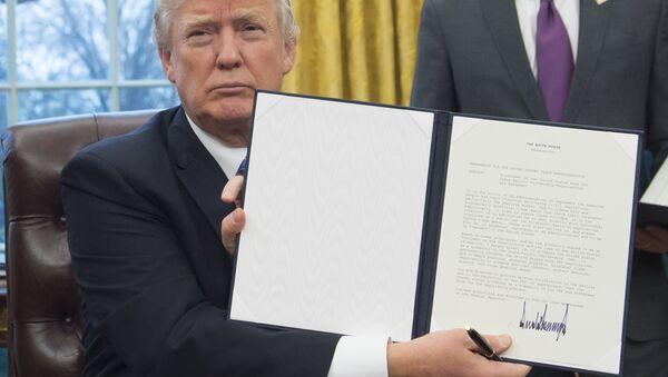 Президент США Дональд Трамп держит в руках распоряжение о выводе США из Транс-Тихоокеанского партнерства после его подписания в Овальном кабинете Белого дома - Sputnik Азербайджан
