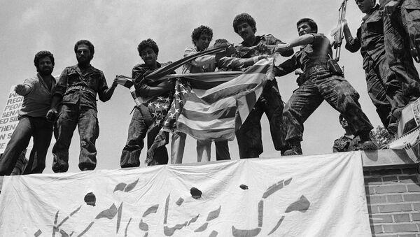 Люди с порванным флагом США стоят на крыше здания посольства Соединенных Штатов в ходе массовых антиамериканских демонстраций в Тегеране, 25 мая 1979 года - Sputnik Азербайджан