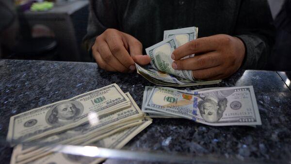 Мужчина пересчитывает 100-долларовые купюры США - Sputnik Азербайджан