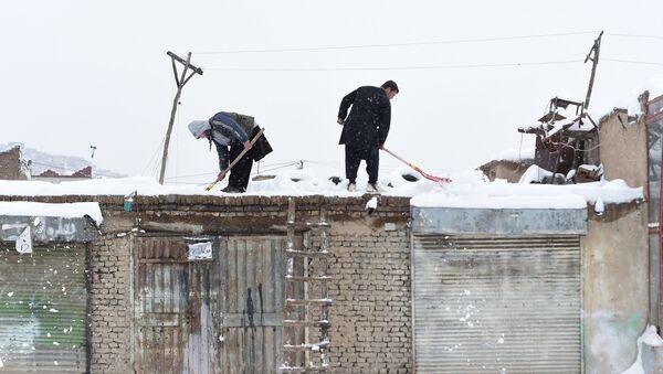 Мужчины убирают снег с крыши своих магазинов после обильного снегопада в Кабуле, 5 февраля 2017 года - Sputnik Азербайджан
