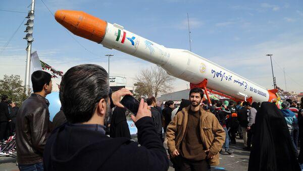 Люди фотографируются у ракеты-носителя Simorgh (Феникс) в день празднования 37-й годовщины Исламской революции, Тегеран, 11 февраля 2016 года - Sputnik Азербайджан