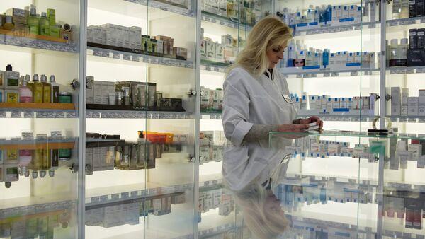 Сотрудница аптеки разбирает лекарства, фото из архива - Sputnik Азербайджан
